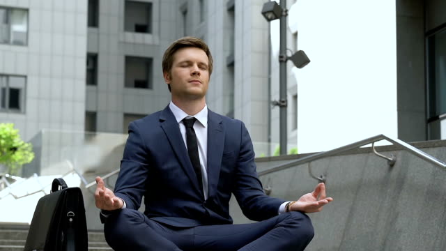 Businessman sits in lotus pose near office building, undistracted, self-control Businessman sits in lotus pose near office building, undistracted, self-control lotus position stock videos & royalty-free footage