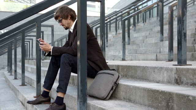 a businessman sits on the steps near a business center and uses a smartphone - кофе брейк стоковые видео и кадры b-roll
