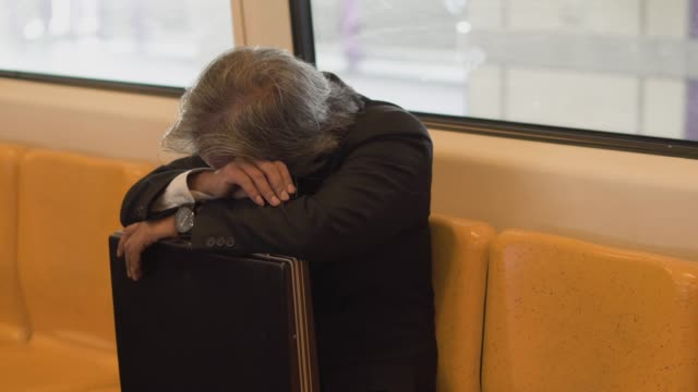 Businessman sitting and napping on the train. Businessman sitting and napping on the train. Because he tired and work hard. exhaustion stock videos & royalty-free footage