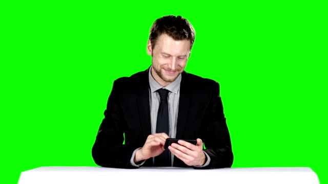 Businessman sitting at the table and uses phone. Green screen video