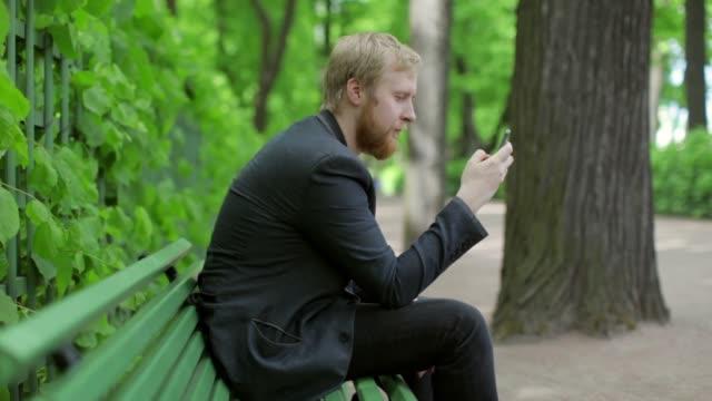 ベンチの公園に座って電話でメッセージを書くビジネスマン - ベンチ点の映像素材/bロール