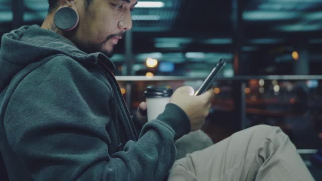 stockvideo's en b-roll-footage met zakenman zittend in de luchthaven en werken met het gebruik van mobiele telefoon 's nachts. - vliegveld vertrekhal