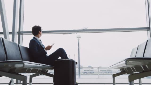 stockvideo's en b-roll-footage met zakenman zittend in luchthaven vertreklounge met bagage met behulp van mobiele telefoon als vliegtuig neemt af door window-shot in slow motion - zakenreis