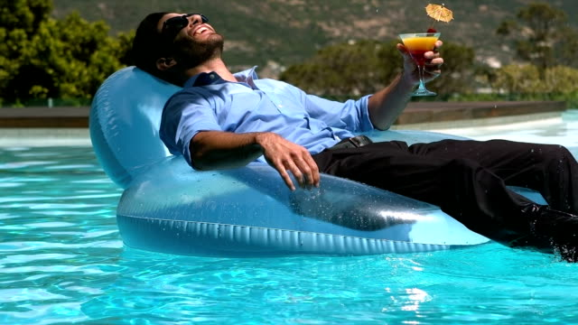 Businessman sitting on buoy while drinking cocktail video