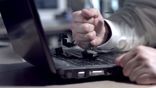 stockvideo's en b-roll-footage met businessman smashing laptop with fist, slow motion - woedend