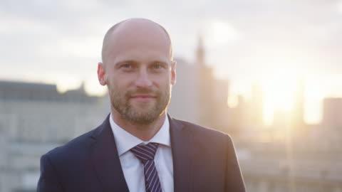 vidéos et rushes de homme d'affaires souriant sur toit - portrait