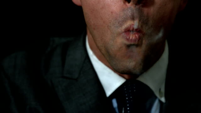 stockvideo's en b-roll-footage met businessman smoking his cigar on black background - guy with cigar