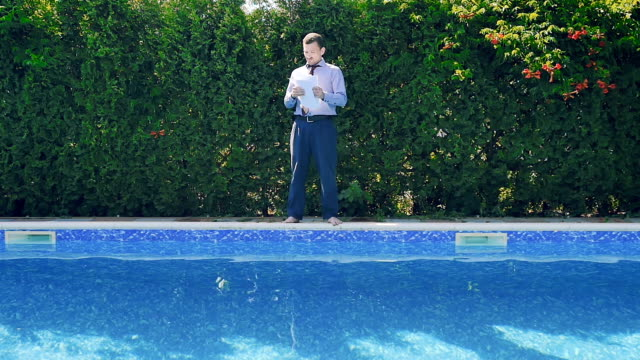 Businessman sorts the documents near swimming pool video