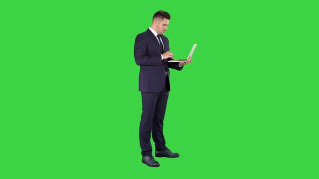 geschäftsmann steht und mit laptop auf einem grünen bildschirm, chroma key - hoch position stock-videos und b-roll-filmmaterial