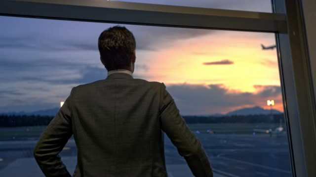 Businessman standing at the window at the airport and observing the planes at sunset
