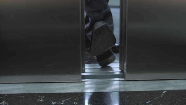 SLO MO DS Businessman stopping the elevator door with his foot video