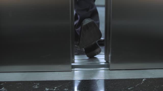 slo mo ds uomo d'affari interrompere la porta dell'ascensore con il piede - ascensore video stock e b–roll