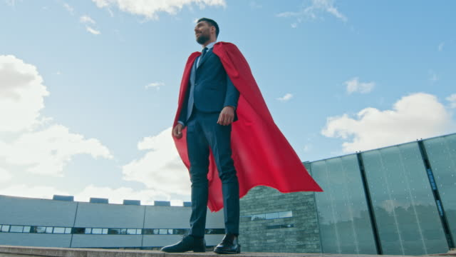 Businessman Superhero WIth Red Cape Blowing in the Wind Stands on the Roof of a Skyscraper Ready to Make Business Transactions and Save the Day. Low Angle Shot.