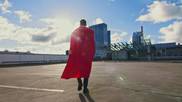 Businessman Superhero WIth Red Cape Blowing in the Wind Walks on the Roof of a Skyscraper Ready to Make Business Transactions and Save the Day. Following Back View Shot.
