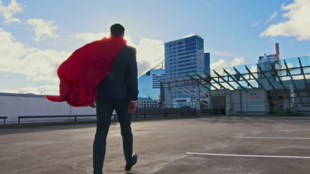 Businessman Superhero With Red Cape Blowing in the Wind Walks on the Roof of a Skyscraper Ready to Save the Day. In the Background Modern City Center. Following Back View Shot.