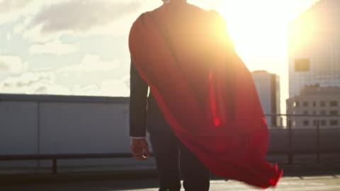 vidéos et rushes de homme d'affaires super-héros avec cape rouge dans le vent se promène sur le toit d'un gratte-ciel, regardant vers le soleil couchant, prêt à sauver la journée. capture de mouvement lent suivante vue arrière. - courage