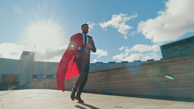 Businessman Superman WIth Red Cape Blowing in the Wind Runs on the Roof of a Skyscraper, Ready to Save the Day. Following Back View Slow Motion Shot.