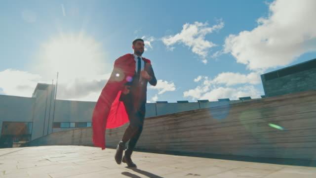 geschäftsmann superman mit roten umhang blowing in the wind läuft auf dem dach eines wolkenkratzers, bereit, den tag zu retten. folgenden rückansicht zeitlupe erschossen. - held stock-videos und b-roll-filmmaterial