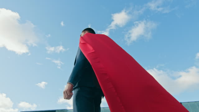 Businessman Superman WIth Red Cape Blowing in the Wind Stands on the Roof of a Skyscraper, Crossed Arms, Ready to Make Business Transactions and Save the Day. Low Angle Shot. Businessman Superman WIth Red Cape Blowing in the Wind Stands on the Roof of a Skyscraper, Crossed Arms, Ready to Make Business Transactions and Save the Day. Low Angle Shot. Shot on RED EPIC-W 8K Helium Cinema Camera. cape garment stock videos & royalty-free footage