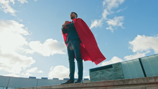 Businessman Superman WIth Red Cape Blowing in the Wind Stands on the Roof of a Skyscraper, Crossed Arms, Ready to Make Business Transactions and Save the Day. Low Angle Shot.