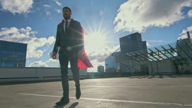 businessman superman with red cape blowing in the wind walks on the roof of a skyscraper ready to save the day. in the background modern city center. following low angle shot. - super hero stock videos & royalty-free footage