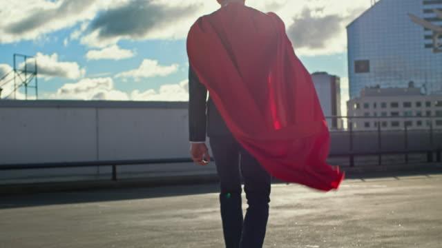 geschäftsmann superman mit roten umhang blowing in the wind geht auf dem dach eines wolkenkratzers, blick in den sonnenuntergang, bereit, den tag zu retten. folgenden rückansicht zeitlupe erschossen. - held stock-videos und b-roll-filmmaterial