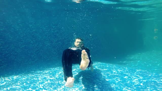 Businessman swims under water in slowmotion video