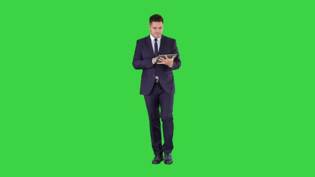 Businessman swiping pages on a tablet and talking to camera explaining something while walking on a Green Screen, Chroma Key