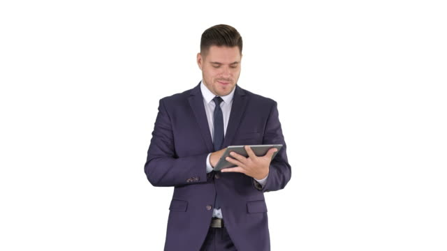 Businessman swiping pages on a tablet and talking to camera explaining something while walking on white background