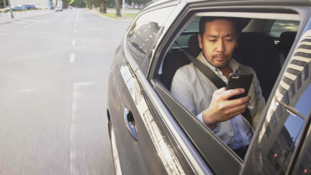 Businessman takes a an Uber ride through the city while using smart phone