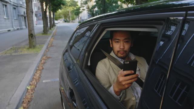 vídeos de stock, filmes e b-roll de empresário leva uma viagem de táxi pela cidade - dividindo carro