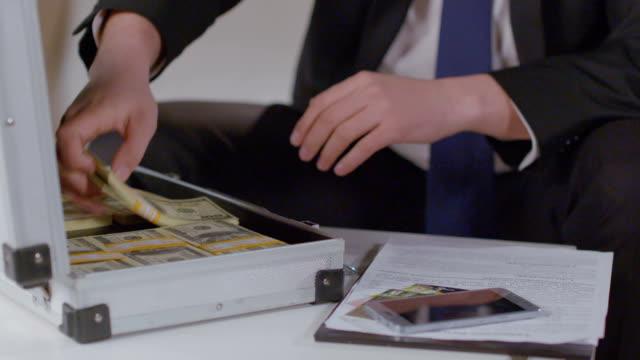 бизнесмен принимает out доллар пакеты из портфель, много денег - dollar bill стоковые видео и кадры b-roll