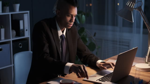 Businessman taking notes while working at night office
