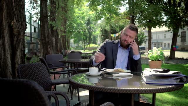 businessman talking by phone during lunch. steadicam shot. - scone filmów i materiałów b-roll