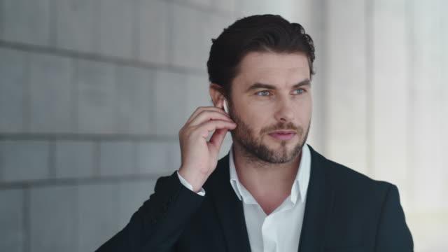 businessman talking by wireless earphones in city. employee using earbuds - auricolari wireless video stock e b–roll