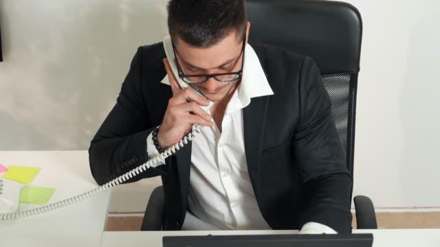 Businessman talking on a desk phone