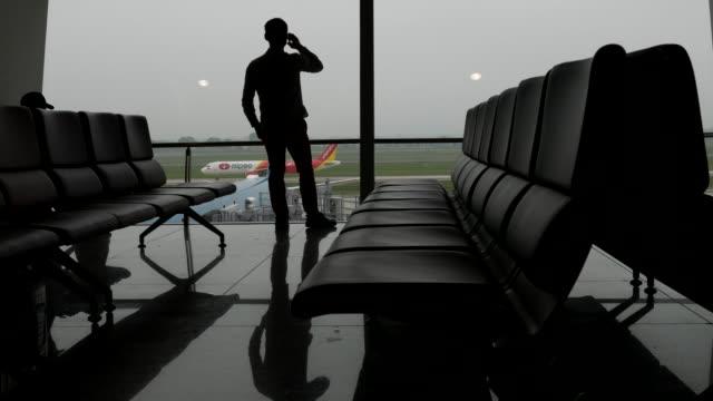 空港の窓口で携帯電話で話しているビジネスマン ビデオ