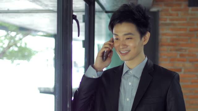 stockvideo's en b-roll-footage met zakenman praten op zijn mobiele telefoon binnen office, dolly schot van links naar rechts en omlaag kantelen - oost azië