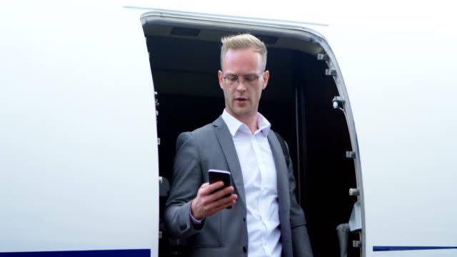 geschäftsmann, telefonieren mit handy während der fahrt von privat-jet 4k - gefreiter stock-videos und b-roll-filmmaterial