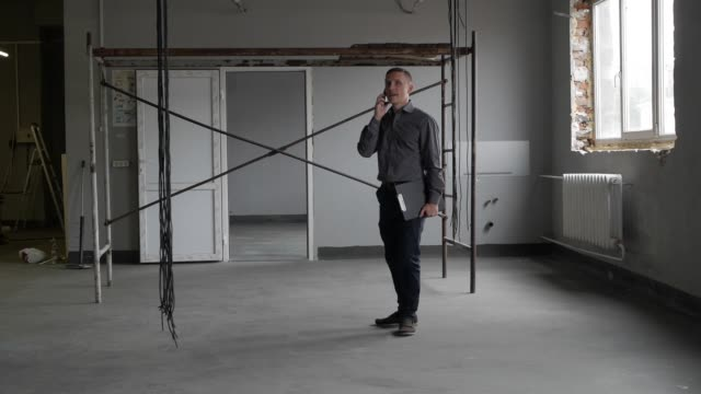 businessman talking on the phone at the construction site A man entrepreneur looks into his smartphone and actively presses his finger on the screen. craftsman architecture stock videos & royalty-free footage