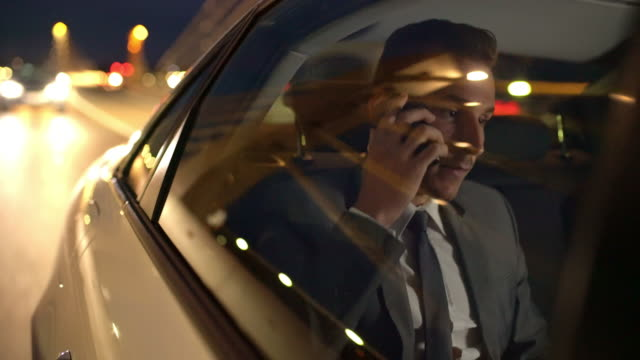 MS Businessman talking on the phone in a limousine Medium shot of a young businessman talking on the phone while sitting in the back seat of a limousine, driving in the city at night. luxury car stock videos & royalty-free footage