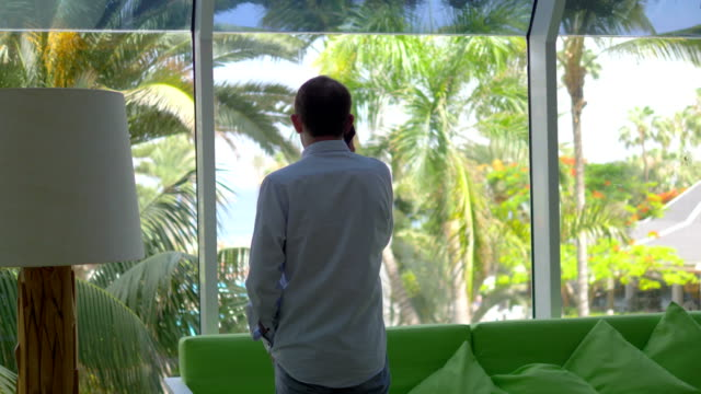 Businessman Talking On The Phone In The Tropics in 4k slow motion 60fps video