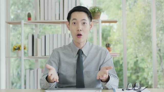 affärsman talar med kamera med leende ansikte, han var nöjd med de högre resultaten. - gestikulera bildbanksvideor och videomaterial från bakom kulisserna