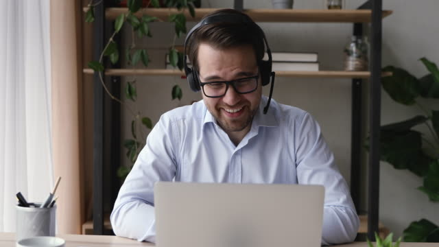 i̇şarkadaşı ile konuşurken iş arkadaşı videocall iletişim kullanarak anekdot üzerinde gülmek - kulaklık seti ses ekipmanı stok videoları ve detay görüntü çekimi
