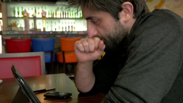 Businessman thinking in a bar video