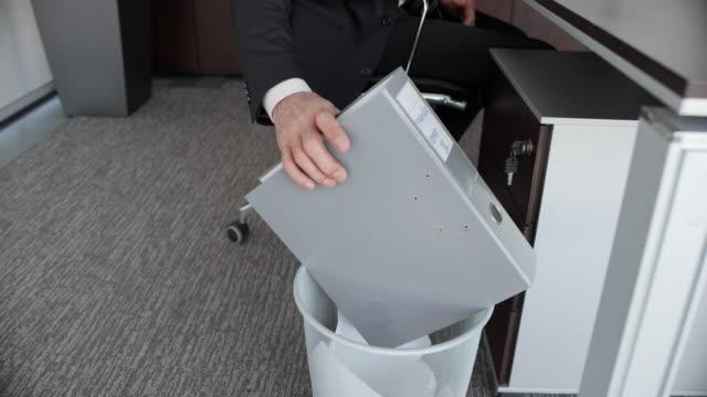vídeos de stock e filmes b-roll de slo mo ds businessman throwing a ring binder into the trash - dossier