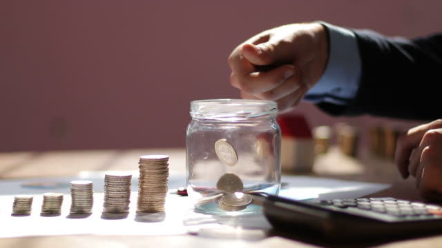 businessman throwing money in glass jar for a plan