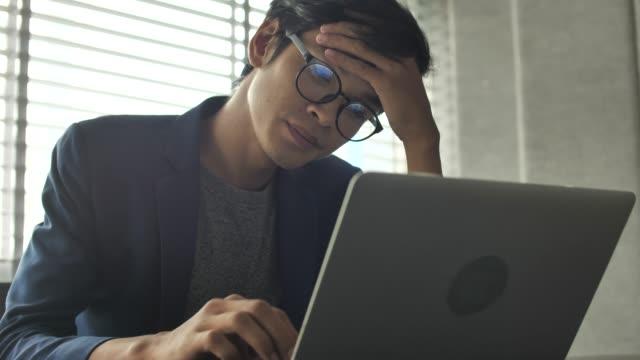 stockvideo's en b-roll-footage met zakenman moe van het kijken op laptop werken - moe