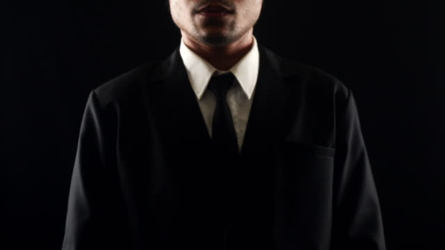 Businessman touching screen with copy space, isolated on black background