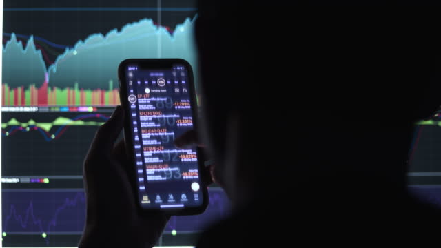 Businessman trading stock market on smart phone in front of stock market financial screen